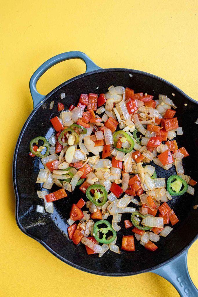 a cast iron skillet filled with sautéed onions, bell peppers, jalapeños and garlic