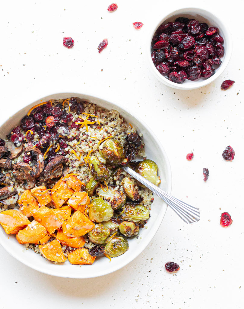 sweet potato quinoa bowl with a fork and a small bowl of dried cranberries off to the side