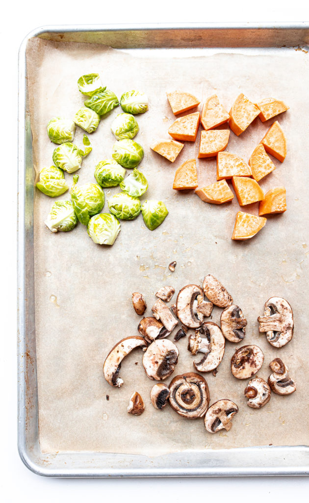 a sheet pan lined with parchment paper filled with mushrooms, sweet potatoes, and brussels sprouts