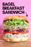 """giant bagel sandwich with a text overlay that reads """"bagel bagel breakfast sandwich"""" and an arrow pointing toward the sandwich"""