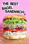 """giant bagel sandwich with a text overlay that reads """"the best bagel sandwich"""" and an arrow pointing toward the sandwich"""