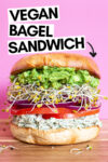 """giant bagel sandwich with a text overlay that reads """"vegan bagel sandwich"""" and an arrow pointing toward the sandwich"""