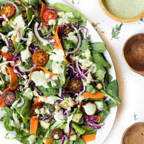"""large round plate with Sweet Tomatoes salad with parsley and dill salad dressing on top surrounded by a bowl of dressing and wooden salad tongs with a text overlay that reads """"vegan garden salad"""""""