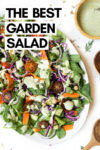 "large round plate with Sweet Tomatoes salad with parsley and dill salad dressing on top surrounded by a bowl of dressing and wooden salad tongs with a text overlay that reads ""the best garden salad"""