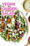"large round plate with Sweet Tomatoes salad with parsley and dill salad dressing on top surrounded by a bowl of dressing and wooden salad tongs with a text overlay that reads ""vegan garden salad"""