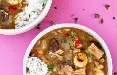 two bowls of vegan gumbo with a pot of rice off to the side