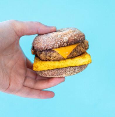 a hand holding a vegan breakfast sandwich
