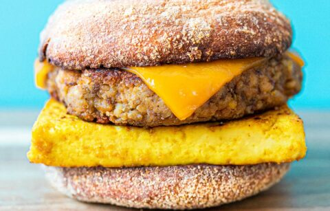 a vegan breakfast with tempeh sausage, tofu egg, and vegan cheese sandwiched between an English muffin