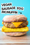 "one vegan breakfast sandwich with a blue background and a text overlay that reads ""vegan sausage egg mcmuffin"" and an arrow pointing toward the sandwich"
