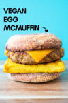 "one vegan breakfast sandwich with a blue background and a text overlay that reads ""vegan egg mcmuffin"" and an arrow pointing toward the sandwich"