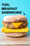 "one vegan breakfast sandwich with a blue background and a text overlay that reads ""tofu breakfast sandwiches!"" and an arrow pointing toward the sandwich"