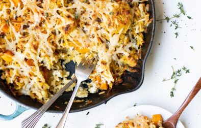 butternut squash orzo bake in a skillet with a serving off to the side on a small plate