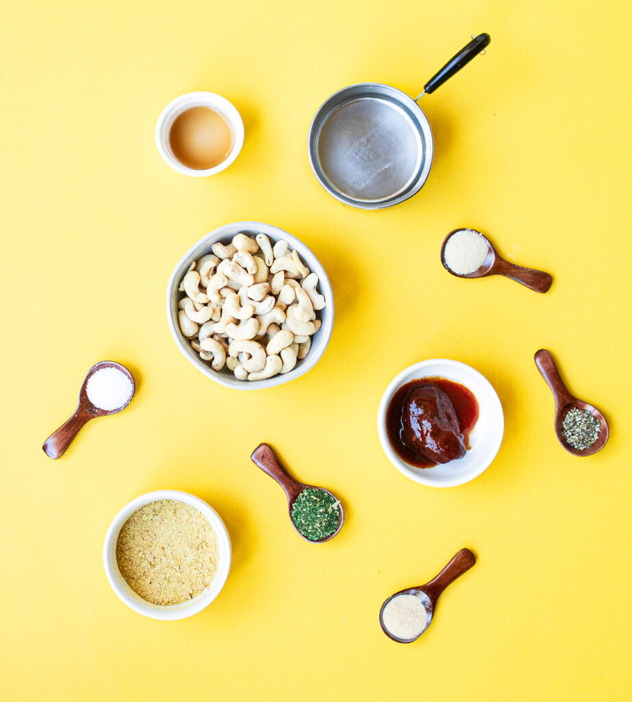 ingredients spread for chipotle ranch dressing including cashews, water, chipotle peppers, onion powder, garlic powder, nutritional yeast, parsley, salt, pepper, and apple cider vinegar