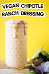 """small mason jar filled with chipotle ranch dressing and some greens off to the side with a text overlay that reads """"vegan chipotle ranch dressing"""""""