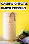 """small mason jar filled with chipotle ranch dressing and some greens off to the side with a text overlay that reads """"cashew chipotle ranch dressing"""""""