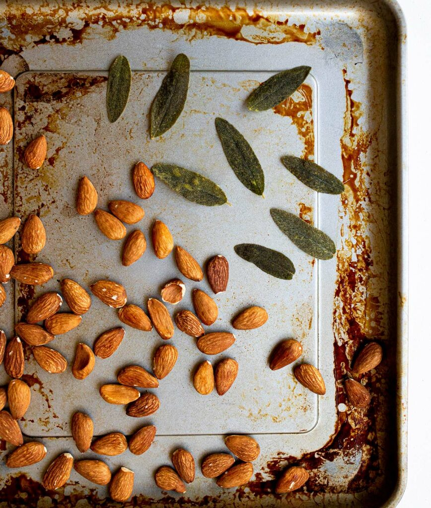 toasted almonds and sage leaves on a baking sheet