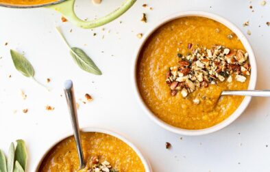 two bowls of pumpkin lentil soup with almond sage crumble and a dutch oven filled with more soup and a small bowl of almond sage crumble off to the side