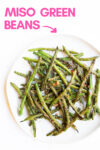 "plate of sesame miso green beans with a text overlay that reads ""miso green beans"" with an arrow pointing toward the plate"