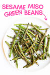 "plate of sesame miso green beans with a text overlay that reads ""sesame miso green beans"" with an arrow pointing toward the plate"