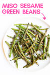 "plate of sesame miso green beans with a text overlay that reads ""miso sesame green beans"" with an arrow pointing toward the plate"