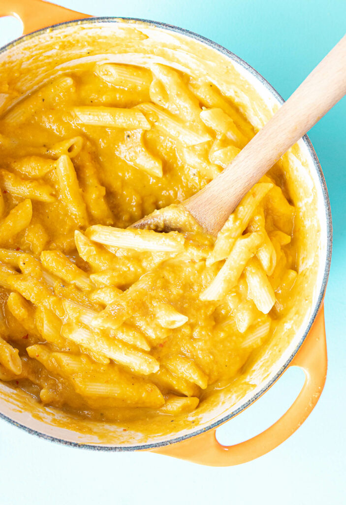 penne in a pot with vegan pumpkin sauce and a wooden spoon