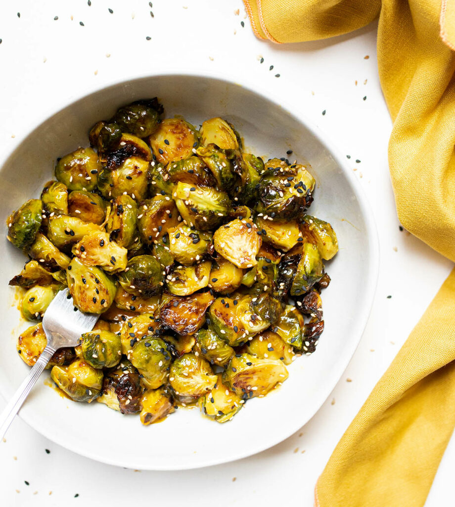bowl of sesame orange brussels sprouts with a yellow cloth napkin