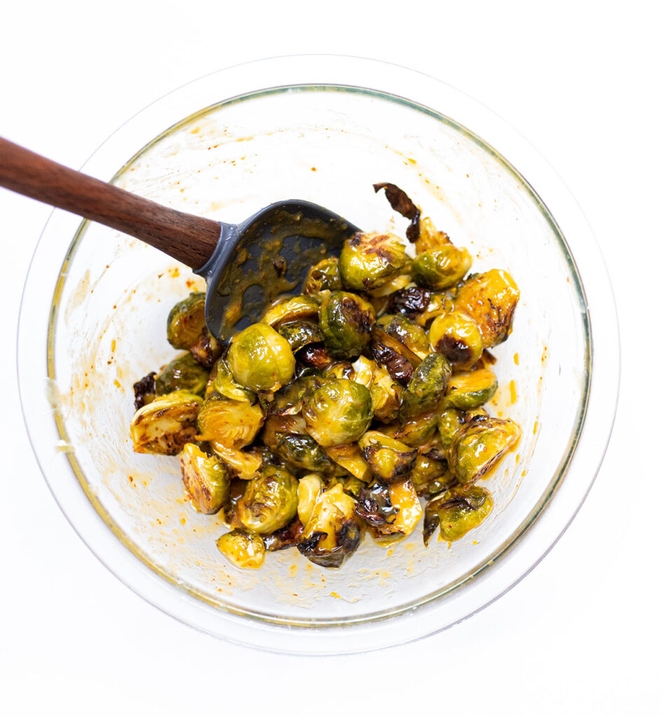 sesame orange brussels sprouts in a medium sized bowl with a silicone spatula