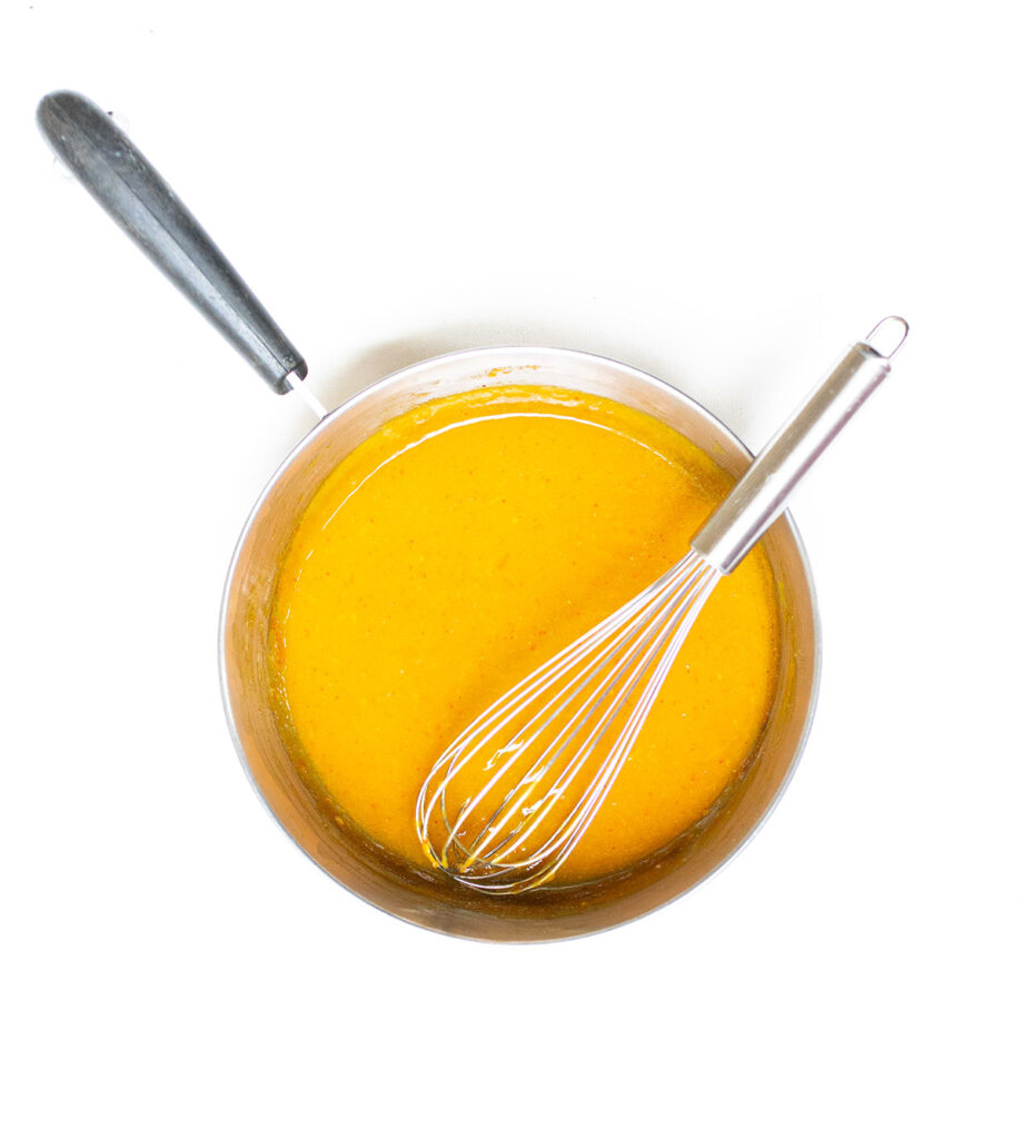 orange sauce in a sauce pan with a whisk