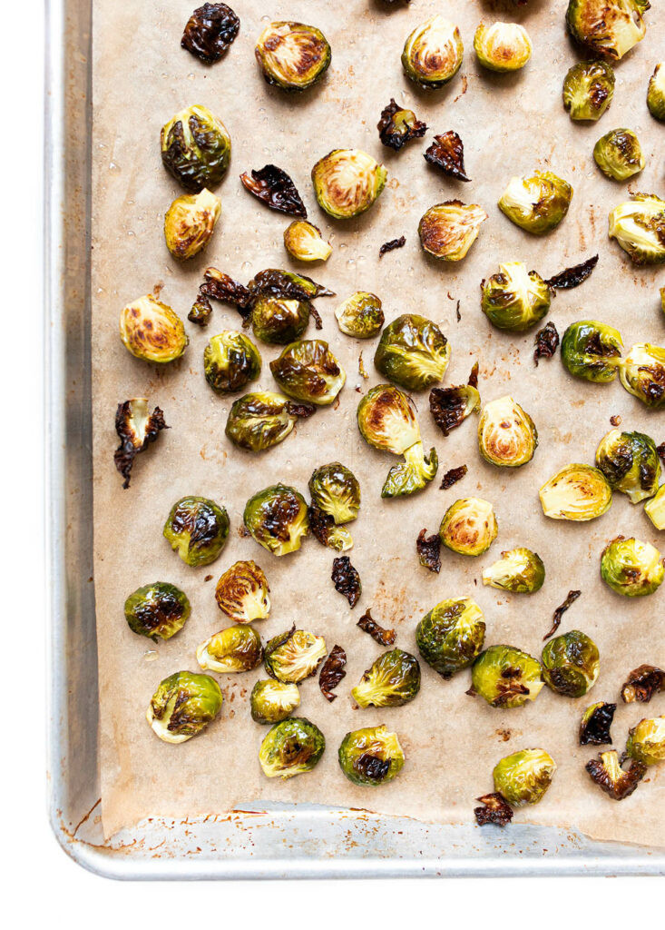 roasted brussels sprout halves on a baking sheet lined with parchment paper