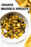 """bowl of sesame orange brussels sprouts with a yellow cloth napkin and a text overlay that reads """"orange brussels sprouts"""""""
