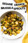 "bowl of sesame orange brussels sprouts with a yellow cloth napkin and a text overlay that reads ""sesame orange brussels sprouts"""