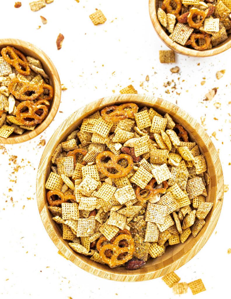 one large bowl and two small bowls filled with sour cream and onion snack mix with small pieces scattered about