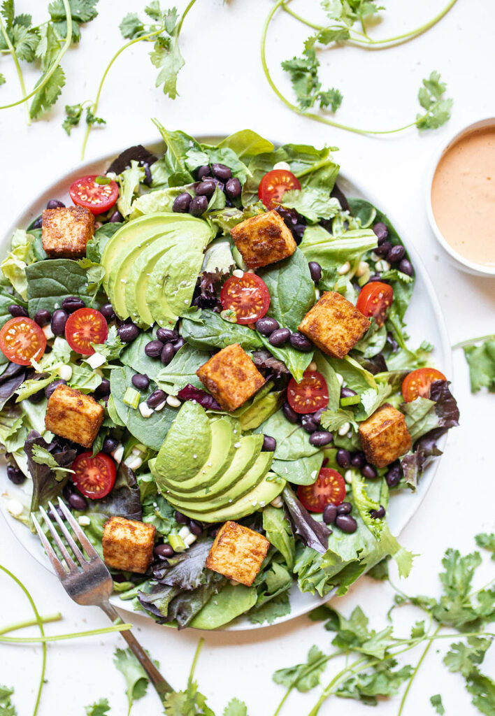 southwest salad with tofu and a fork surrounded by cilantro leaves and a bowl of chipotle ranch dressing