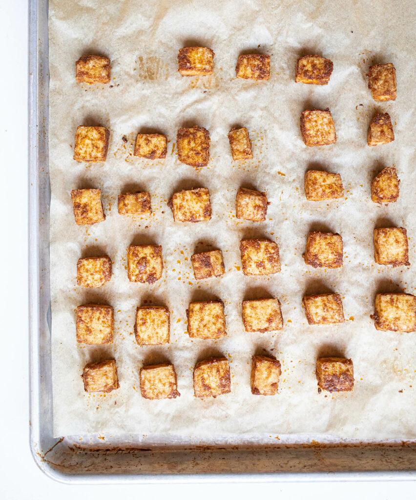 crispy seasoned tofu nuggets on a baking sheet