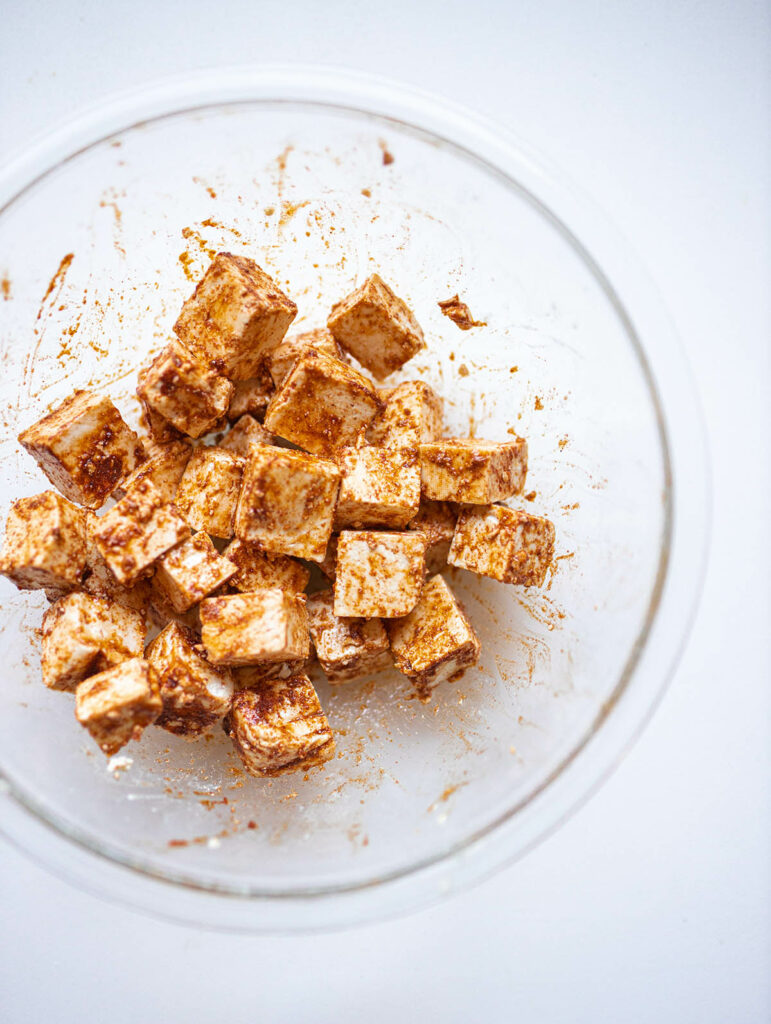 tofu cubes in a bowl with taco seasoning, cornstarch, and olive oil