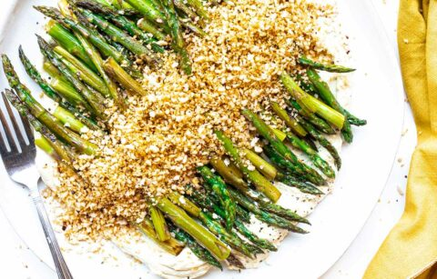 a plate of stovetop asparagus with tofu ricotta and spicy bread crumbs with a fork and a cloth napkin