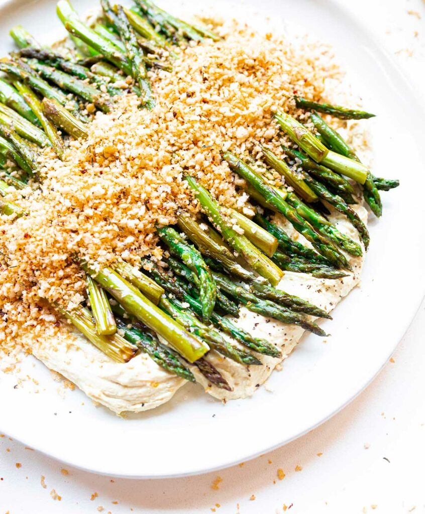 plate of stovetop asparagus with tofu ricotta and spicy bread crumbs at a 45 degree angle