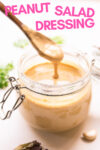 "container of peanut salad dressing with a spoon full of dressing dripping into the container and a text overlay that reads ""peanut salad dressing"""