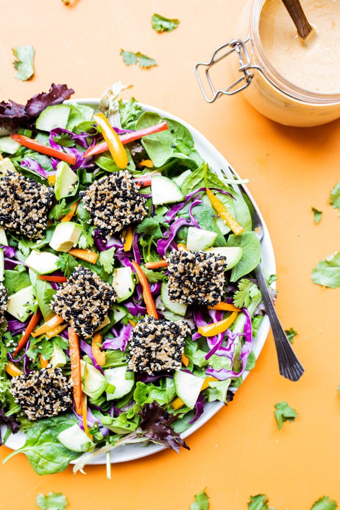 a plate of sesame crusted tofu salad with peanut dressing off to the side