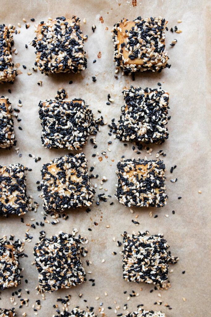 sesame crusted tofu pieces on a baking sheet lined with parchment paper
