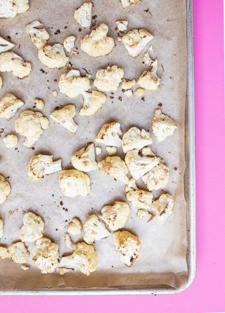 roasted cauliflower on a baking sheet lined with parchment paper
