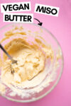 """bowl of miso butter with a spoon and a text overlay that reads """"vegan miso butter"""" and an arrow pointing toward the bowl"""