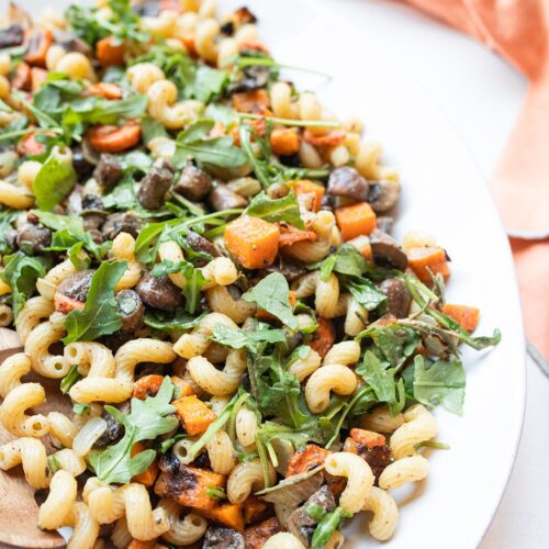 winter vegetable pasta salad on a serving plate with a coral colored napkin off to the side