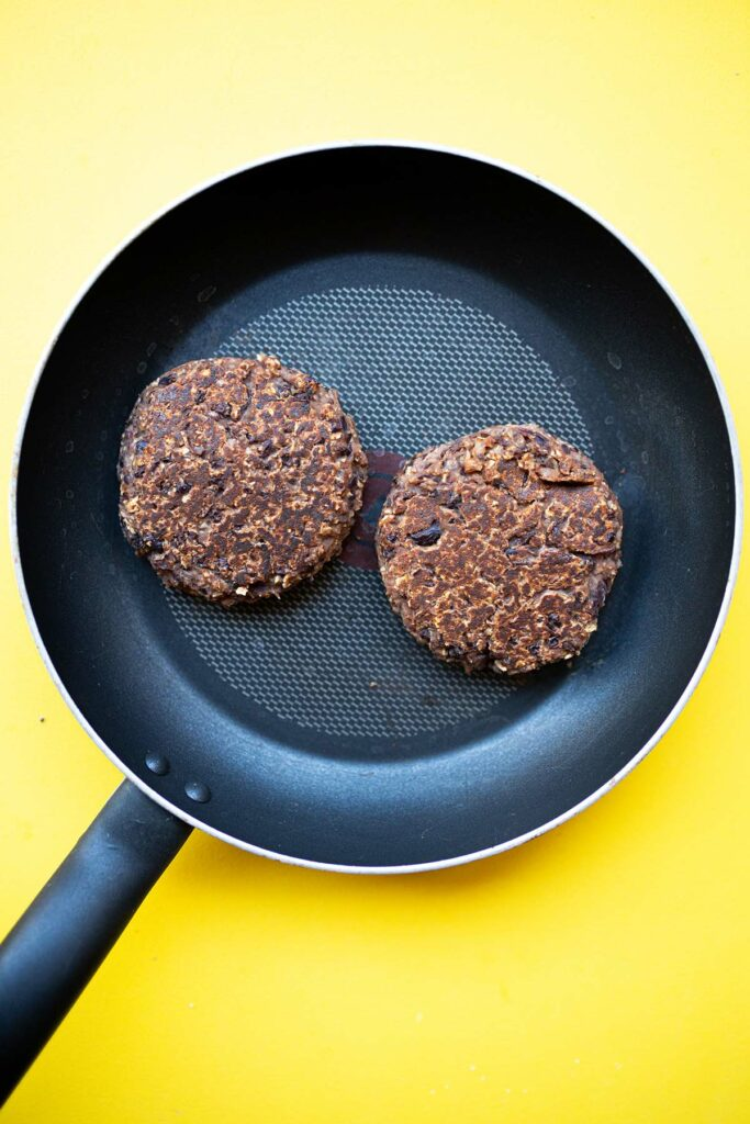 oil-free black bean burger patties in a nonstick skillet