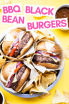 """three oil-free black bean burgers in a cake tin with tortilla chips and a text overlay that reads """"BBQ Black Bean Burgers"""""""