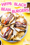 """three oil-free black bean burgers in a cake tin with tortilla chips and a text overlay that reads """"WFPB Black Bean Burgers"""""""