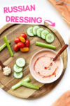 "vegan Russian dressing in a bowl surrounded by chopped fresh veggies with a text overlay that reads ""russian dressing"""