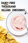 "vegan thousand island dressing on a plate with a spoon and a cloth napkin, lemon slices, and relish off to the side and a text overlay that reads ""dairy-free thousand island dressing"""