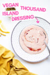 "vegan thousand island dressing on a plate with a spoon and a cloth napkin, lemon slices, and relish off to the side and a text overlay that reads ""vegan thousand island dressing"""