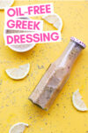 "overhead shot of a bottle of oil-free greek dressing and some of the dressing in a ramekin off to the side surrounded by herbs and lemon slices and a text overlay that reads ""oil-free greek dressing"""
